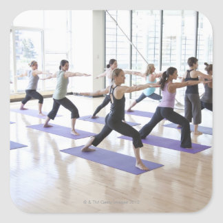 Yoga instructor teaching a class of women the square sticker