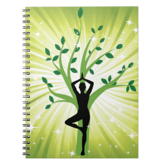 Yoga on green with growing tree notebook