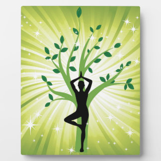 Yoga on green with growing tree plaques