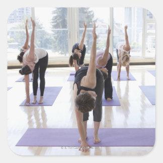 yoga practicante de la clase con el instructor en colcomanias cuadradases