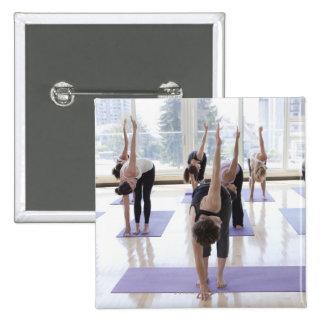 yoga practicante de la clase con el instructor en pin cuadrado