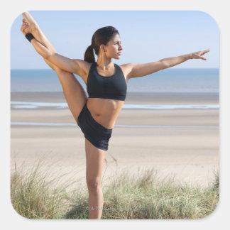 yoga practicante de la mujer en llevar de la playa pegatina cuadrada