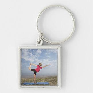 Yoga practicante de la mujer por la playa llavero cuadrado plateado