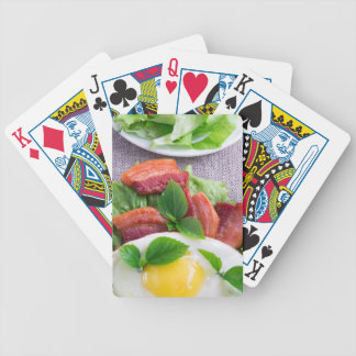 Yolk, fried bacon, herbs and lettuce close-up bicycle playing cards