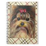 Yorkshire Terrier y cuaderno de la tela escocesa