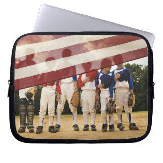 Young baseball players partially hidden by laptop computer sleeves