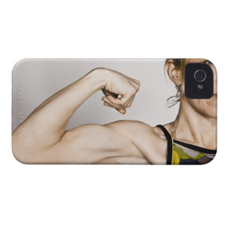 Young blond female flexes bicep muscle while iPhone 4 covers