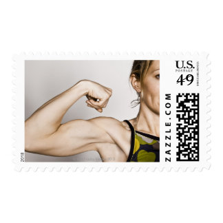 Young blond female flexes bicep muscle while postage