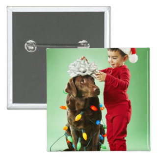 Young boy wrapping Christmas lights around a dog Button