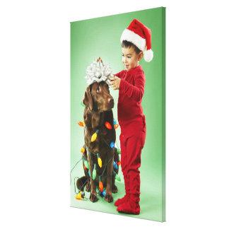 Young boy wrapping Christmas lights around a dog Canvas Print