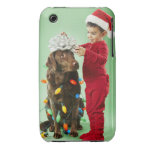 Young boy wrapping Christmas lights around a dog iPhone 3 Covers