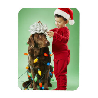 Young boy wrapping Christmas lights around a dog Magnet