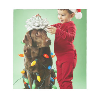 Young boy wrapping Christmas lights around a dog Notepads