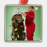 Young boy wrapping Christmas lights around a dog Christmas Tree Ornament