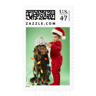 Young boy wrapping Christmas lights around a dog Postage