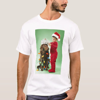 Young boy wrapping Christmas lights around a dog T-Shirt