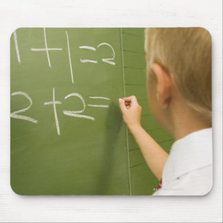 Young Caucasian Boy Writing on a Classroom Mouse Pad