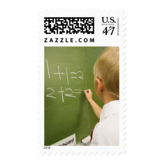 Young Caucasian Boy Writing on a Classroom Postage
