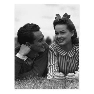 Young couple lying on grass postcard