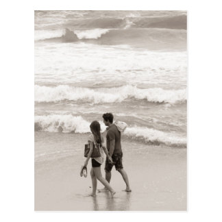 Young couple walking on the beach postcard