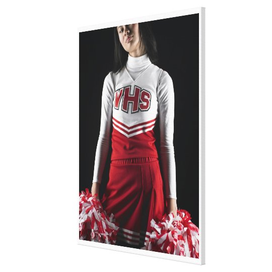 Young female cheerleader holding pom-poms, mid canvas print