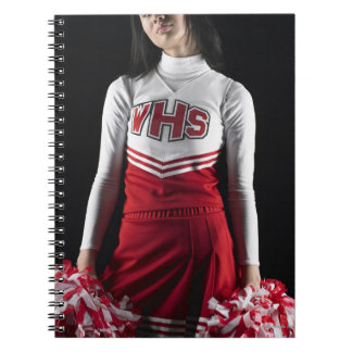 Young female cheerleader holding pom-poms, mid notebook