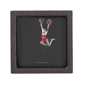 Young female cheerleader jumping in midair, arms 2 gift box