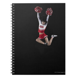 Young female cheerleader jumping in midair, arms 2 notebook