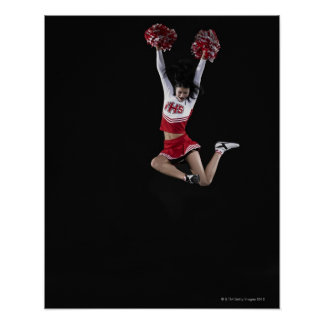 Young female cheerleader jumping in midair, arms 2 poster