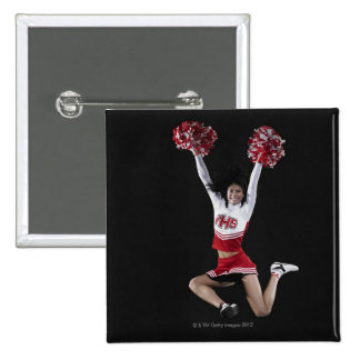 Young female cheerleader jumping in midair, arms button