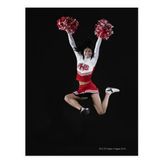 Young female cheerleader jumping in midair, arms post cards