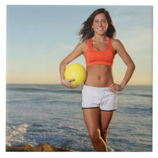 young fit pretty female holding a volleyball at tile