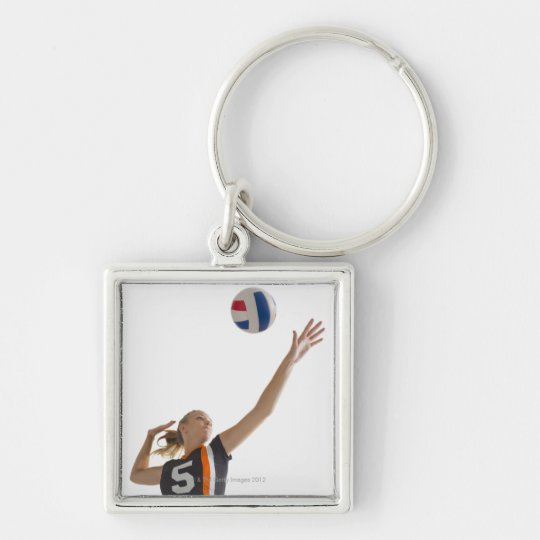 Young girl (16-17) playing volleyball keychain