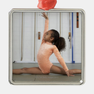 Young girl gymnast practicing her floor metal ornament
