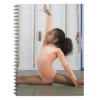Young girl gymnast practicing her floor spiral notebooks