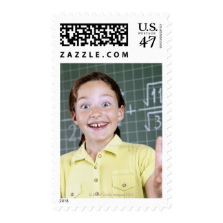 young girl in front of blackboard having idea postage