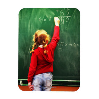 young girl writing on a blackboard magnet