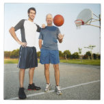 Young man and senior man on outdoor basketball large square tile