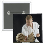 Young man breaking boards with karate chop on button