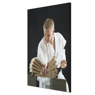 Young man breaking boards with karate chop on canvas print