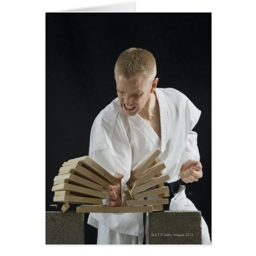 Young man breaking boards with karate chop on greeting cards
