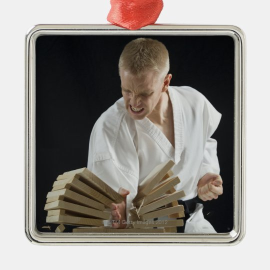 Young man breaking boards with karate chop on metal ornament