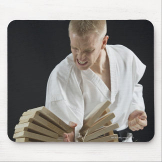 Young man breaking boards with karate chop on mouse pad