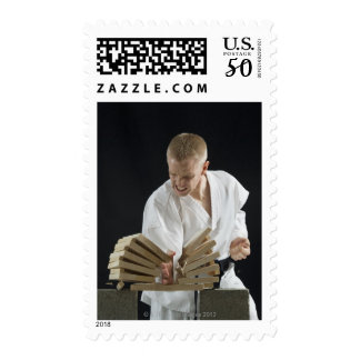 Young man breaking boards with karate chop on postage