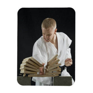 Young man breaking boards with karate chop on rectangular photo magnet