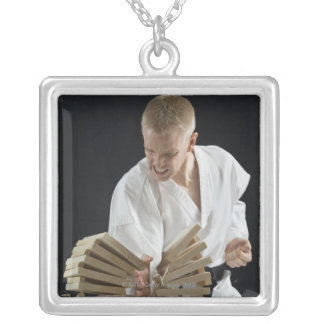 Young man breaking boards with karate chop on silver plated necklace
