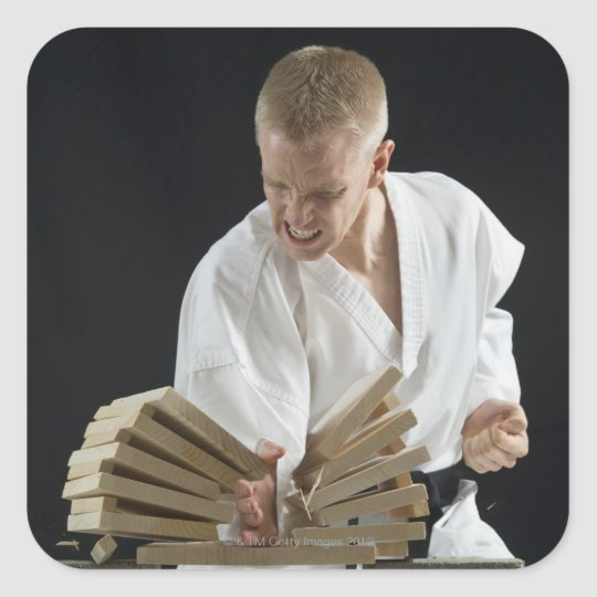 Young man breaking boards with karate chop on square sticker