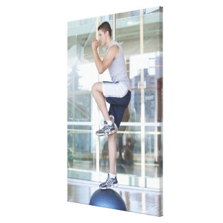 young man doing step-up exercises on a balance canvas print