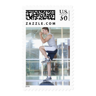 young man doing step-up exercises on a balance postage
