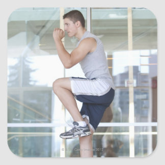 young man doing step-up exercises on a balance square sticker